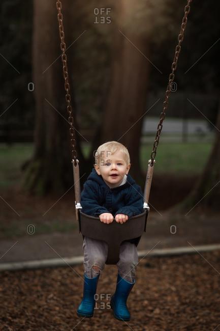 Blonde toddler boy swinging in a baby swing