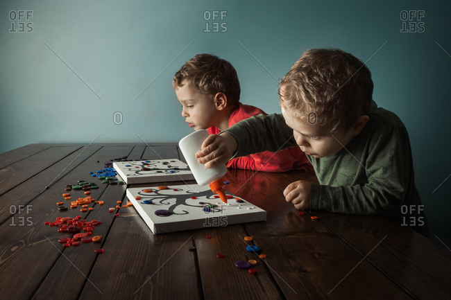 Two boys gluing buttons onto canvases