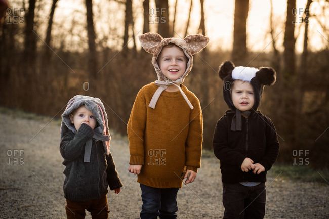 Three adorable young children wearing animal bonnets