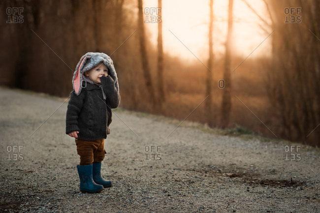 Toddler walking on path in the woods wearing a bunny rabbit bonnet