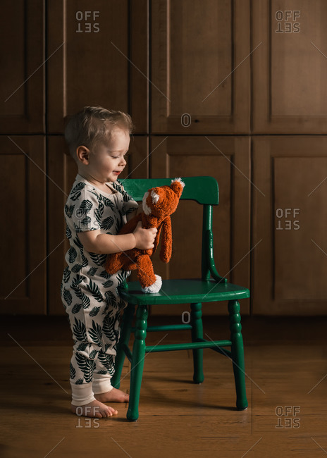 Toddler boy standing by green chair holding a stuffed toy fox