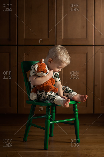 Toddler boy sitting in a green chair holding a stuffed toy fox