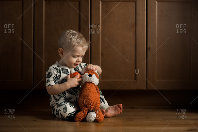 Toddler boy sitting on floor with stuffed toy fox while eating an apple