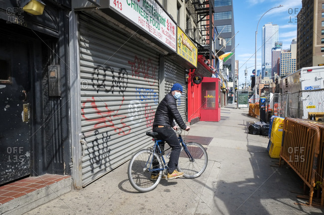 New York City, New York, USA - March 21, 2020: Man wearing mask while riding bike on city street during the Coronavirus outbreak