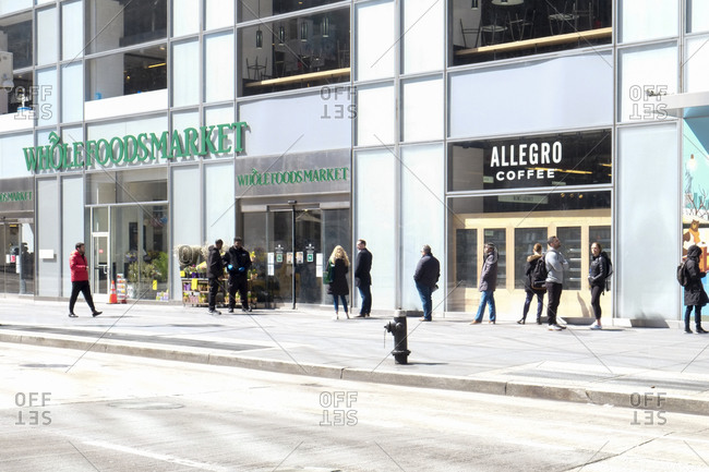 New York City, New York, USA - March 21, 2020: Spaced out line outside of Whole Foods Market due to social distancing during the Coronavirus outbreak