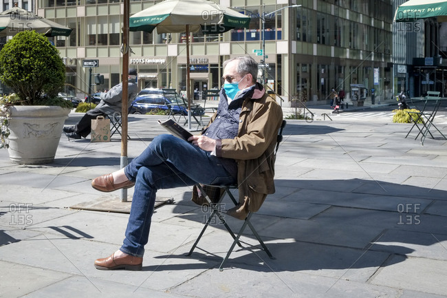New York City, New York, USA - March 21, 2020: Man wearing mask while sitting in chair in Bryant Park reading a magazine during the Coronavirus outbreak