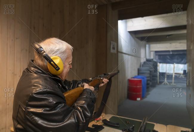 Senior man aiming with a gun in shooting range