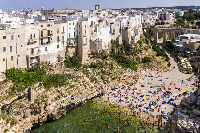 Italy- Polignano a Mare- Aerial view of crowd of people relaxing on sandy beach of coastal town in summer