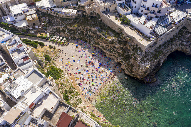 June 11, 2019: Italy- Polignano a Mare- Aerial view of crowd of people relaxing on sandy beach of coastal town in summer