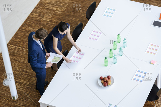 Businessman and woman preparing boardroom for a meeting- elevated view