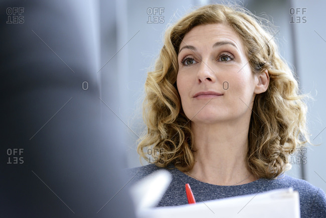 Senior businesswoman talking to colleagues in a business meeting- portrait