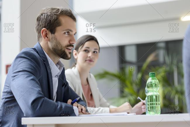 Business people sitting in meeting- working focused