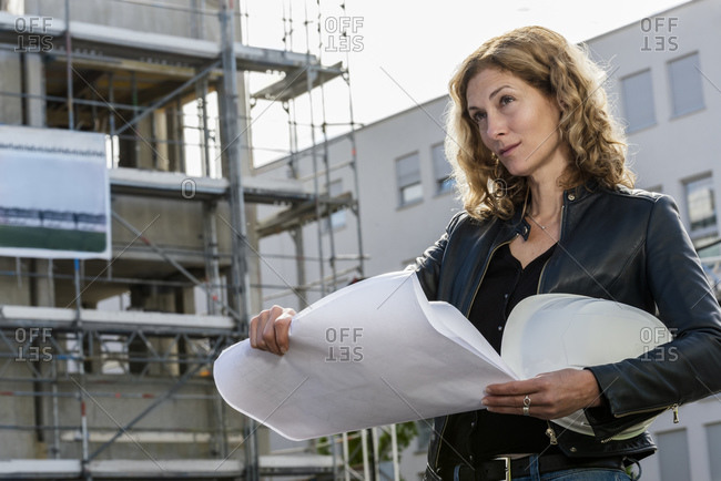 Female architect looking at construction plan