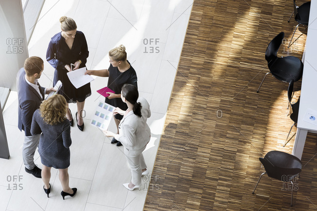 Business people standing in modern office building discussing project