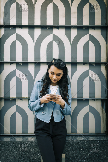 Portrait of young woman with long black hair standing in front of patterned wall using smartphone