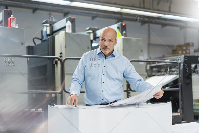 Businessman in a printing plant looking around