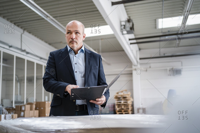 Businessman holding a folder in a factory