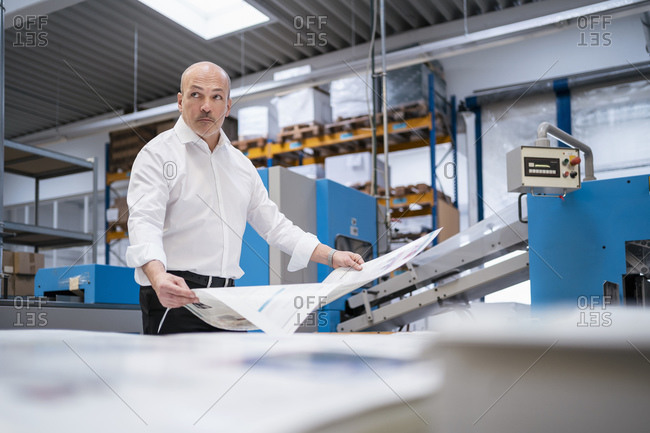 Businessman in a printing plant holding paper