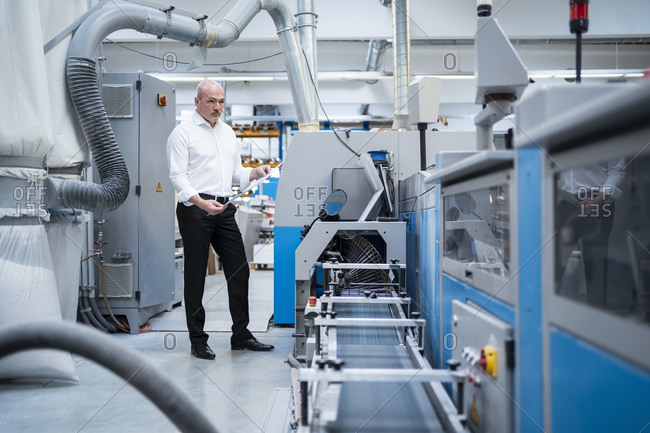 Businessman standing at a machine in a factory