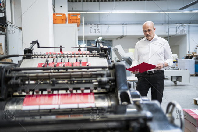 Businessman in a printing plant checking product