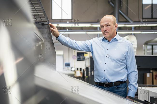 Businessman at a machine in a factory