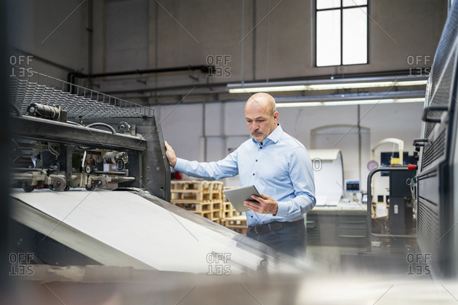 Businessman with tablet examining machine in a factory