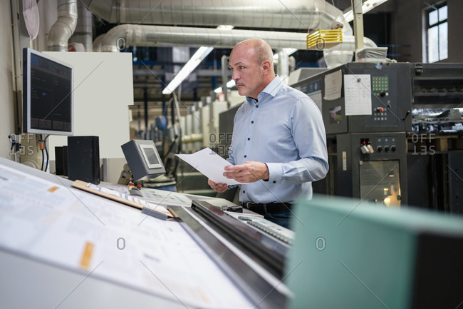 Businessman holding paper at a machine in a factory