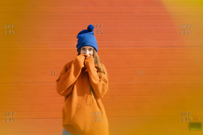 Portrait of teenage girl wearing blue woolly hat and orange sweater in front of orange background