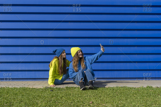 Two teenage girls wearing matching clothes taking selfie with smartphone in front of blue background