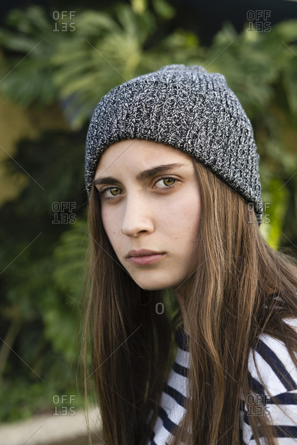 Portrait of serious teenage girl with long brown hair wearing grey wooly hat