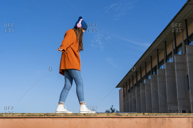 Teenage girl balancing on a wall against while listening music with headphones