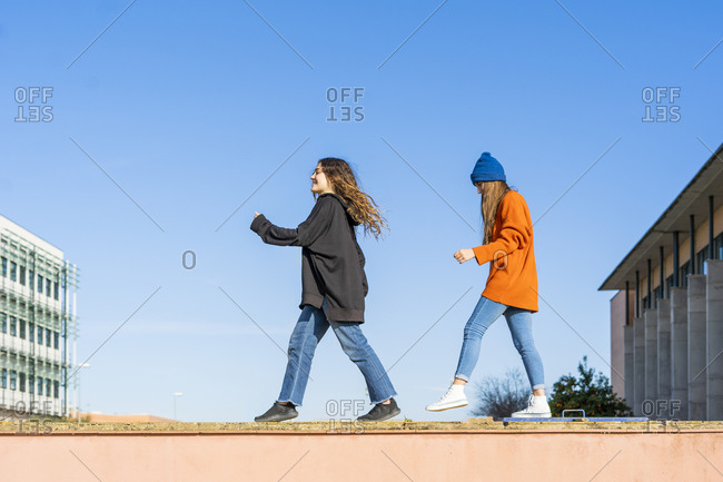 Two teenage girls walking on a wall against sky