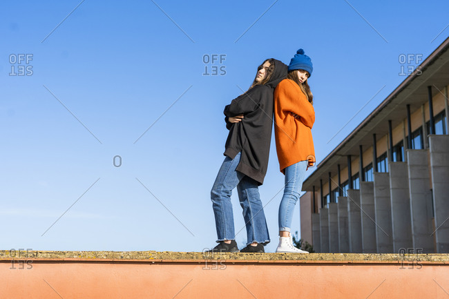 Two teenage girls standing back to back on a wall against blue sky