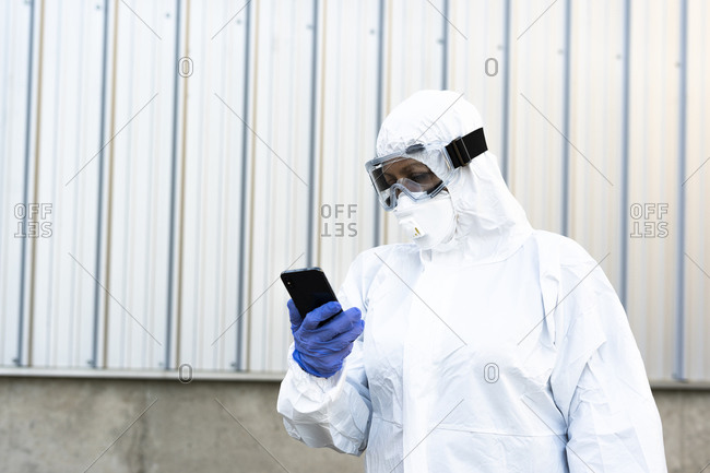 Female scientist wearing protective suit and mask and looking at smartphone