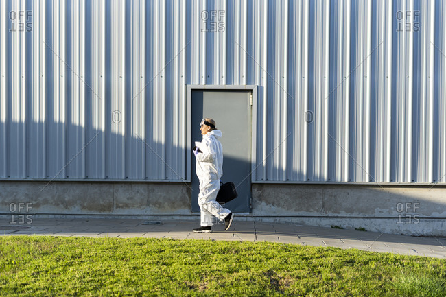 Female scientist wearing protective suit in front of a laboratory