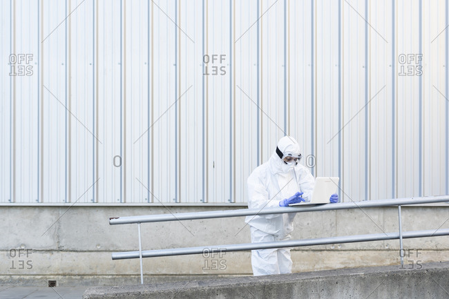 Female scientist wearing protective suit and mask