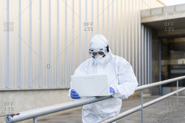Female scientist wearing protective suit and mask and using laptop in front of the laboratory