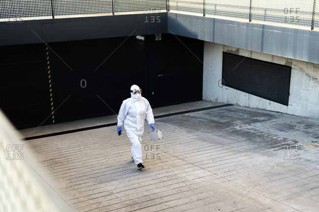 Female scientist wearing protective suit and mask and walking at a garage