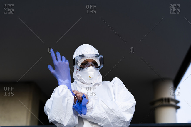 Female scientist wearing protective suit and mask and putting on protective gloves