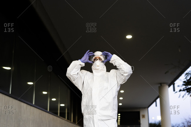 Female scientist wearing protective suit and mask and safety glasses
