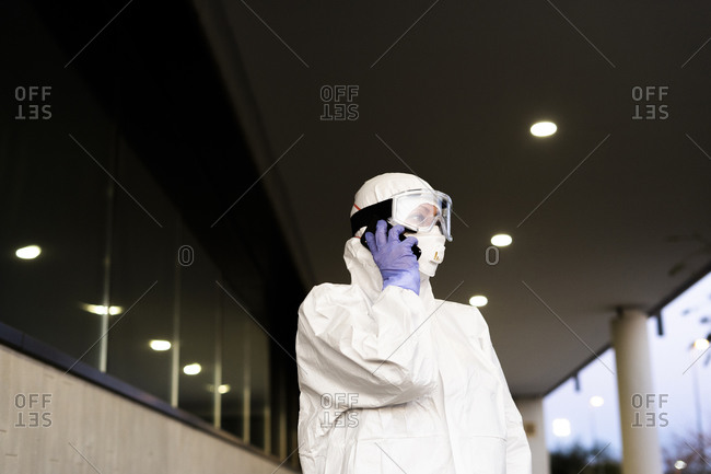 Female scientist wearing protective suit and mask and using smartphone
