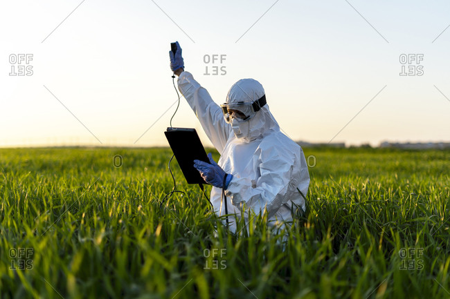 Female scientist researching in field and using measuring device