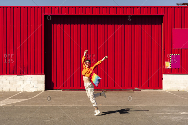 Lesbian with colorful shopping bag in front of a red wall