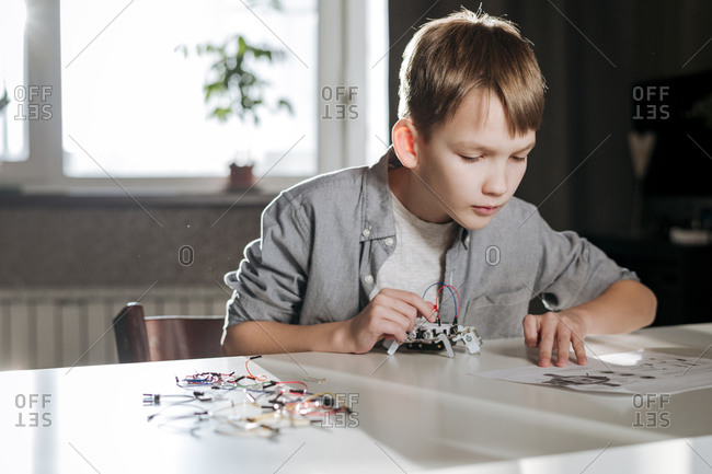 Boy making robot up with instruction at home