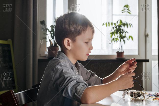 Boy assembling robot at home