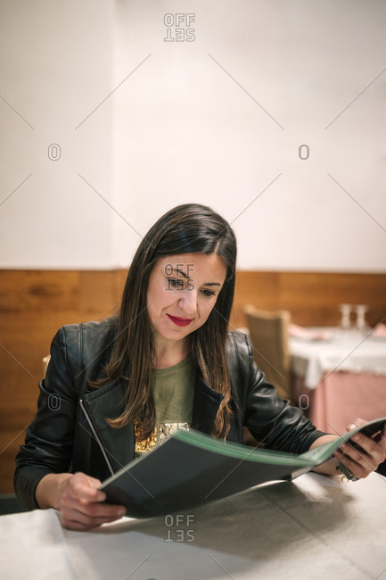 Portrait of smiling woman looking at menu in a restaurant