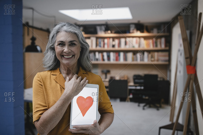 Smiling grey-haired woman holding tablet with a heart on the screen