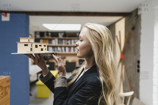 Young businesswoman in loft office holding architectural model
