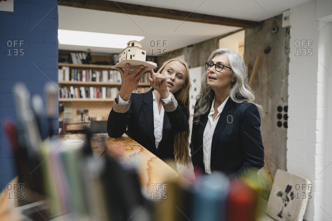 Mature and young businesswoman examining architectural model in loft office