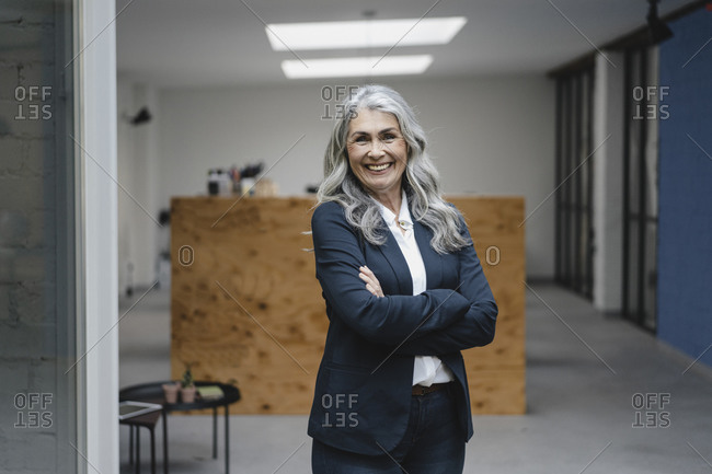 Portrait of smiling grey-haired businesswoman in a loft office